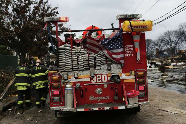 Firefighters work on a fire at a building after Hurricane Sandy on October 30, 2012 in the Rockaway section of the Queens borough of New York City. At least 40 people were reportedly killed in the U.S. by Sandy as millions of people in the eastern United States have awoken to widespread power outages, flooded homes and downed trees. New York City was hit especially hard with wide spread power outages and significant flooding in parts of the city. Photo: Spencer Platt, Getty Images / 2012 Getty Images