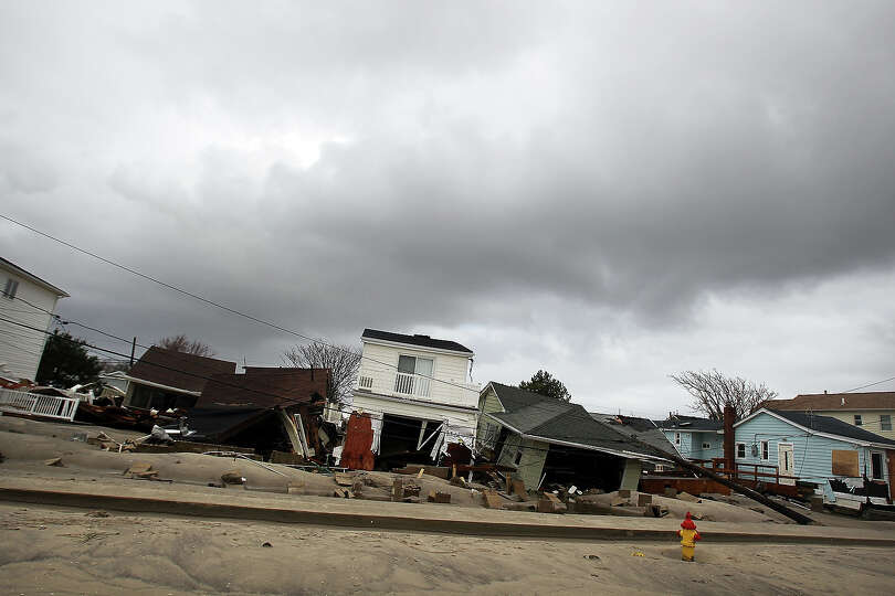 Damaged houses sit on a street on October 30, 2012 in the Breezy Point Neighborhood of the Que