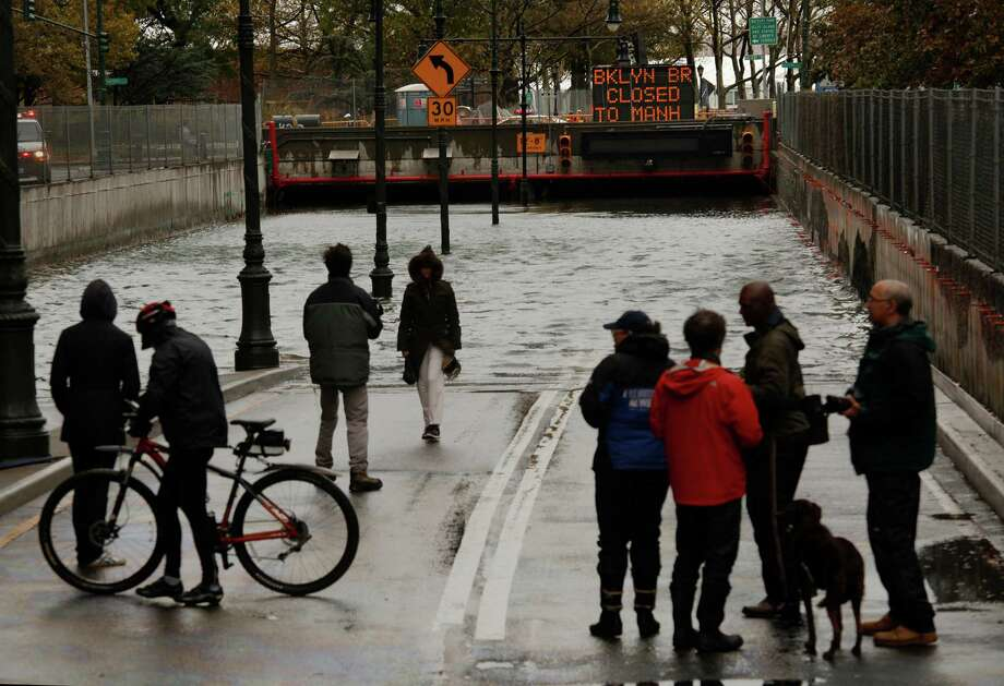 Here at the tip of Manhattan, pedestrians stared agog Tuesday at the entrance to the Brookly-Battery Tunnel, filled nearly to the top with standing water left by the storm surge of Hurricane Sandy. Photo: Carolyn Cole, MBR / ARCHIVE