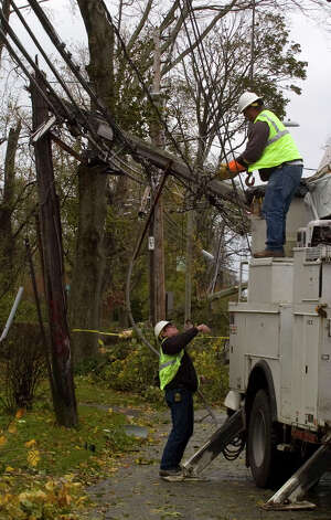 Utility workers from Kansas City work to repair damage along Shippan Avenue in Stamford, Conn., caused by the effects of Hurricane Sandy on Tuesday, Oct. 30, 2012. Photo: Jason Rearick