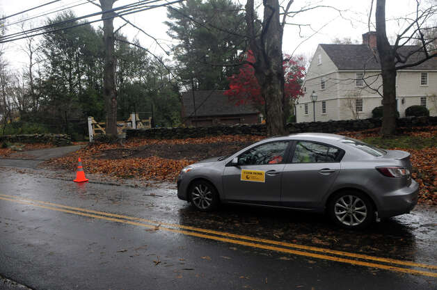 "A ""Power Patrol"" official from Connecticut Light and Power keeps an eye on downed power lines on Scofieldtown Road after Hurricane Sandy related weather in Stamford, Conn., Oct. 30, 2012. Photo: Keelin Daly"