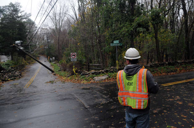 An AT&T crew assesses the broken poles at the intersection of Chestnut Hill Road and Scofieldtown Road after Hurricane Sandy related weather in Stamford, Conn., Oct. 30, 2012. Photo: Keelin Daly