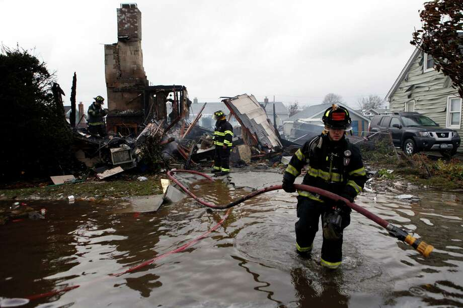 Firefighters work at the scene of a house fire in the aftermath of superstorm Sandy, Tuesday, Oct. 30, 2012, in Lindenhurst, N.Y. According to firefighters at the scene, four homes were destroyed by fire overnight in Lindenhurst, and six in Massapequa. Photo: Jason DeCrow, Associated Press / FR103966 AP