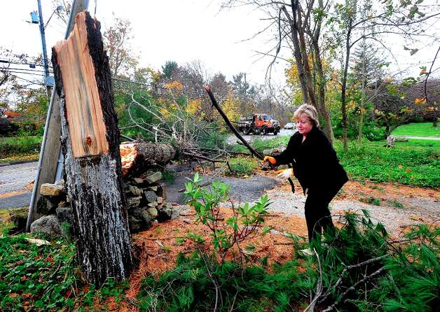 Homeowner Nancy Coppola clears debris from the tree that fell outside her Danbury, Conn. home during Hurricane Sandy Tuesday, Oct. 30, 2012. Photo: Michael Duffy / The News-Times