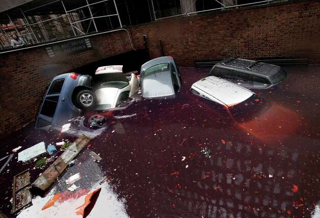 Cars are submerged at the entrance to a parking garage in New York's Financial District in the aftermath of superstorm Sandy, Tuesday, Oct. 30, 2012. New York City awakened Tuesday to a flooded subway system, shuttered financial markets and hundreds of thousands of people without power a day after a wall of seawater and high winds slammed into the city, destroying buildings and flooding tunnels.   (AP Photo/Richard Drew) Photo: Richard Drew