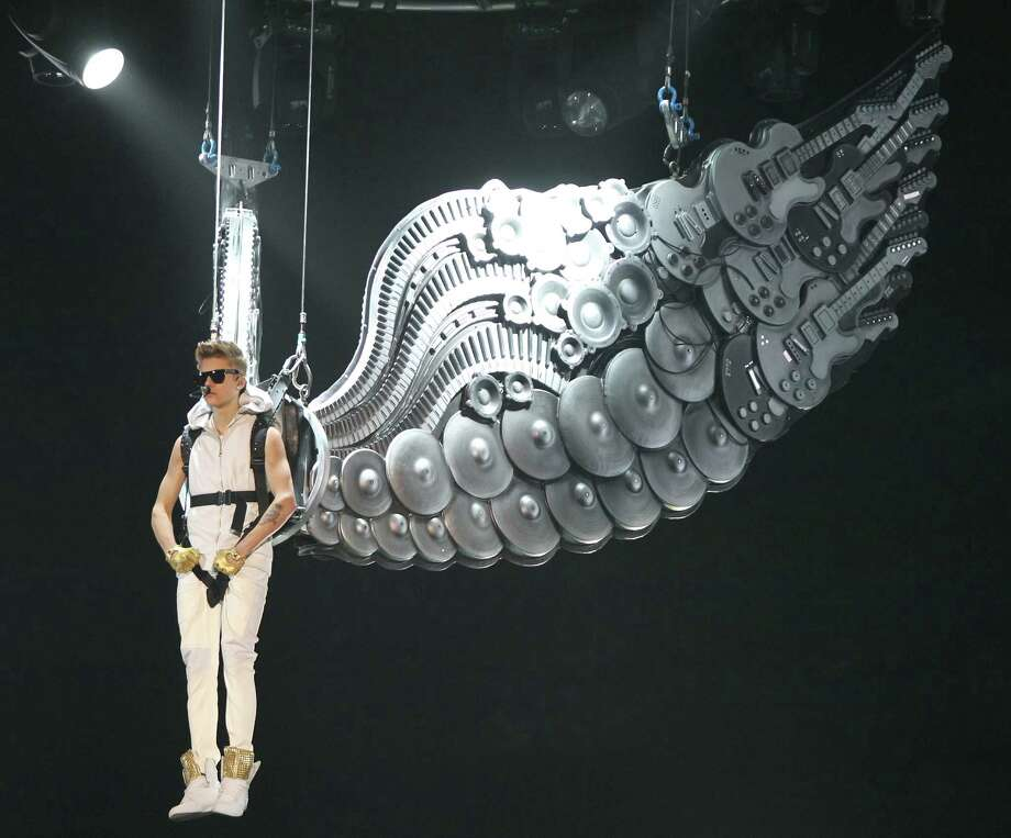 Justin Bieber is lifted out on metallic wings for a sold out crowd, Tuesday, Oct. 30, 2012, in the Toyota Center in Houston. Bieber's new album Believe is out now. Photo: Nick De La Torre, Houston Chronicle / © 2012  Houston Chronicle