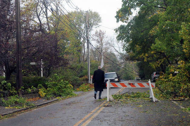 A man walks beneath downed wires along Shore Road after weather from Hurricane Sandy in Old Greenwich, Conn., Oct. 30, 2012. Photo: Keelin Daly