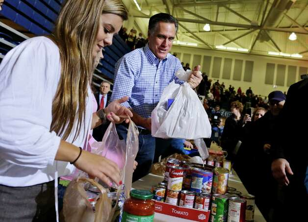 Republican presidential candidate, former Massachusetts Gov. Mitt Romney holds bags of food as he participates in a campaign event collecting supplies from residents local relief organizations for victims of superstorm Sandy, Tuesday, Oct. 30, 2012, at the James S. Trent Arena in Kettering, Ohio. (AP Photo/Charles Dharapak) Photo: Charles Dharapak