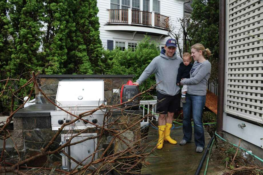 Joel Lusman with his son David, 17 months, and wife Sarah work on their house after the hurricane Sandy in Old Greenwich, Tuesday, Oct, 30, 2012. Photo: Helen Neafsey / Greenwich