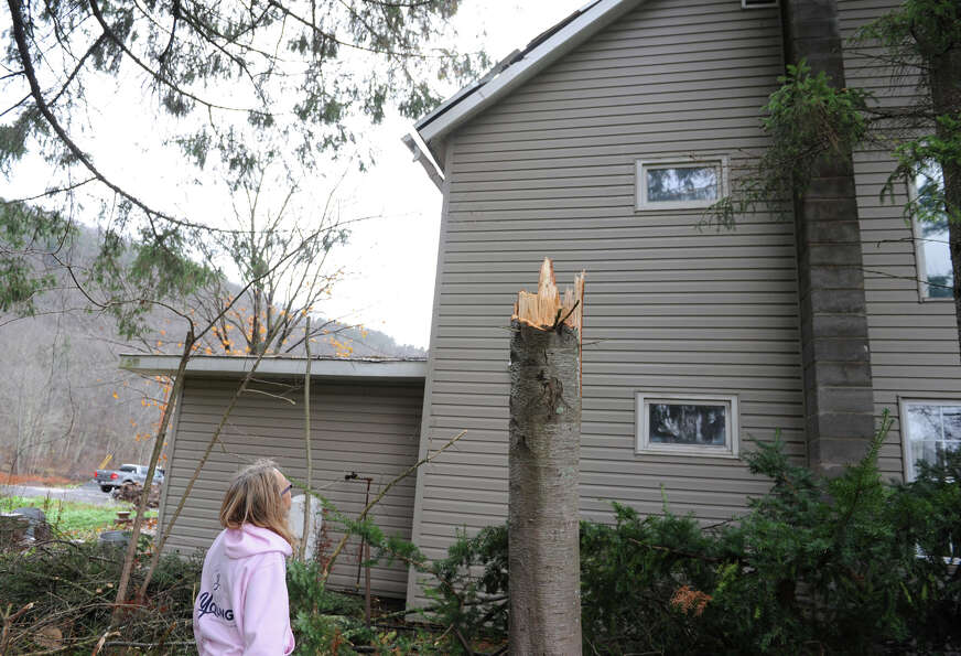 Peggy Young looks at the damage on her roof from a fallen caused by Hurricane Sandy's wind on Tuesda