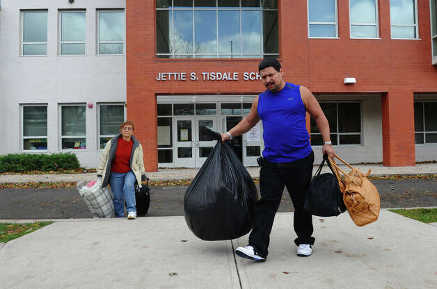 Wilson Duque and his grandmother Maria Martinez leave the shelter set up at Jettie Tisdale School in Bridgeport, Conn. on Tuesday October 30, 2012. Photo: Christian Abraham