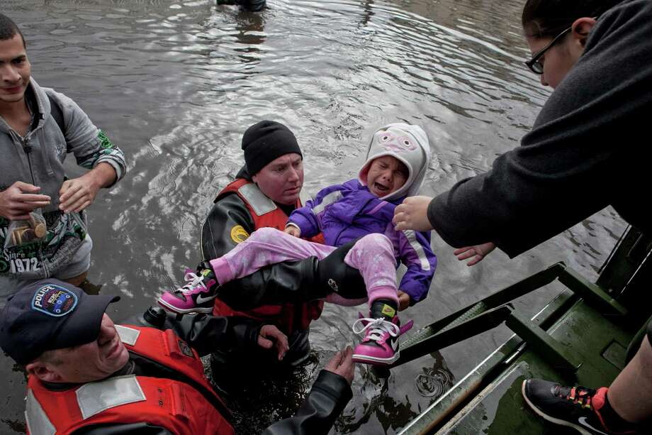 Members of a New York Police Department tactical team rescue Haley Rombi, 3, in the Dongon Hills neighborhood of the Staten Island borough of New York, Oct. 30, 2012. As Hurricane Sandy churned inland as a downgraded storm, residents up and down the battered mid-Atlantic region woke on Tuesday to lingering waters, darkened homes and the daunting task of cleaning up from storm surges and their devastating effects. (Michael Kirby Smith/The New York Times) Photo: MICHAEL KIRBY SMITH / NYTNS