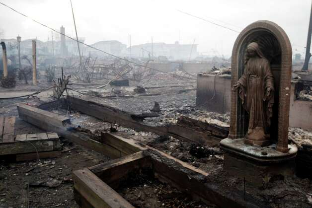 Damage caused by a fire at Breezy Point is shown Tuesday, Oct. 30, 2012, in New York. A fire department spokesman says more than 190 firefighters are at the blaze in the Breezy Point section. Fire officials say the blaze was reported around 11 p.m. Monday in an area flooded by the superstorm that began sweeping through earlier. (AP Photo/Frank Franklin II) Photo: Frank Franklin II