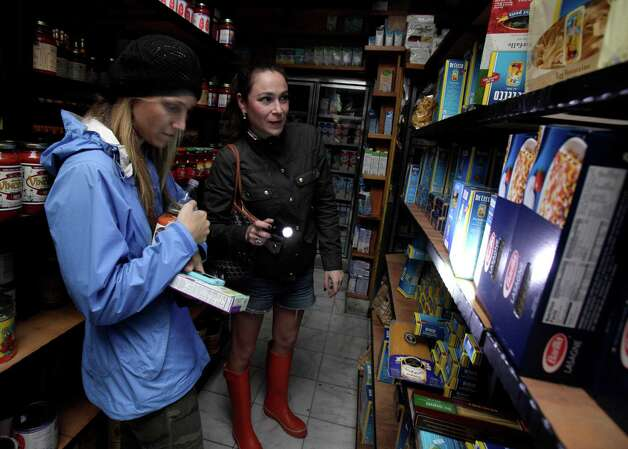 Two women shop for groceries by flashlight in the Tribeca neighborhood of New York, Tuesday, Oct. 30, 2012. ConEd cut power Moday to some neighborhoods served by underground lines as the advancing storm surge from Hurricane Sandy threatened to flood substations. Floodwaters later led to explosions that disabled a substation in Lower Manhattan, cutting power tens of thousands of customers south of 39th Street. (AP Photo/Richard Drew) Photo: Richard Drew