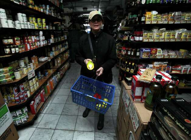 A woman shops for groceries by flashlight in the Tribeca neighborhood of New York, Tuesday, Oct. 30, 2012. ConEd cut power to some neighborhoods served by underground lines as the advancing storm surge from Hurricane Sandy threatened to flood substations. Floodwaters later led to explosions that disabled a substation in Lower Manhattan, cutting power tens of thousands of customers south of 39th Street. (AP Photo/Richard Drew) Photo: Richard Drew