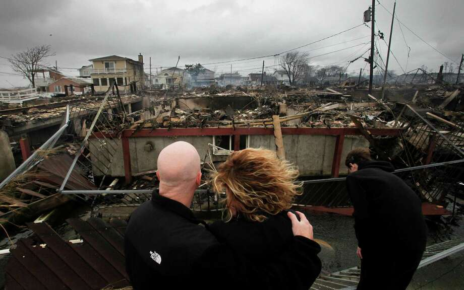Robert Connolly, left, embraces his wife Laura as they survey the remains of the home owned by her parents that burned to the ground in the Breezy Point section of New York, Tuesday, Oct. 30, 2012. More than 50 homes were destroyed in the fire which swept through the oceanfront  community during superstorm Sandy. At right is their son, Kyle. (AP Photo/Mark Lennihan) Photo: Mark Lennihan