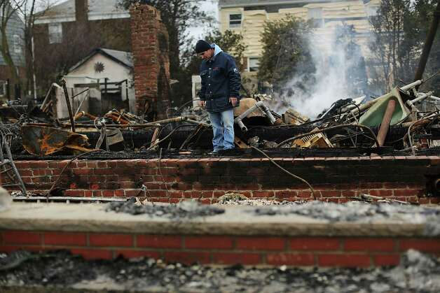 NEW YORK, NY - OCTOBER 30:  A  man looks through the debris of his destroyed home after Hurricane Sandy on October 30, 2012 in the Rockaway section of the Queens borough of New York City. At least 40 people were reportedly killed in the U.S. by Sandy as millions of people in the eastern United States have awoken to widespread power outages, flooded homes and downed trees. New York City was hit especially hard with wide spread power outages and significant flooding in parts of the city.  (Photo by Spencer Platt/Getty Images) Photo: Spencer Platt