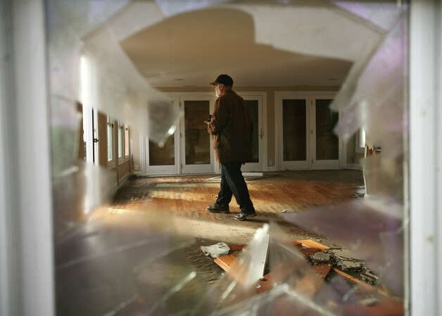 Phillip Givens walks quietly through his destroyed waterfront home, knocked off its foundations by flood waters from Hurricane Sandy, on Point Beach Drive in Milford on Tuesday, October 30, 2012. Photo: Brian A. Pounds