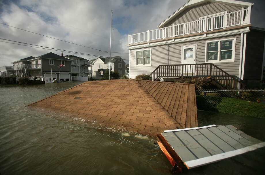 The roof from a garage destroyed by Hurricane Sandy floats at the intersection of Point Beach Drive and Elaine Road in Milford on Tuesday, October 30, 2012. Photo: Brian A. Pounds