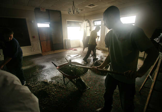Workers shovel sand and gravel left by Hurricane Sandy from the dining room at Costa Azzurra Restaurant on Broadway in Milford on Tuesday, October 30, 2012. Photo: Brian A. Pounds