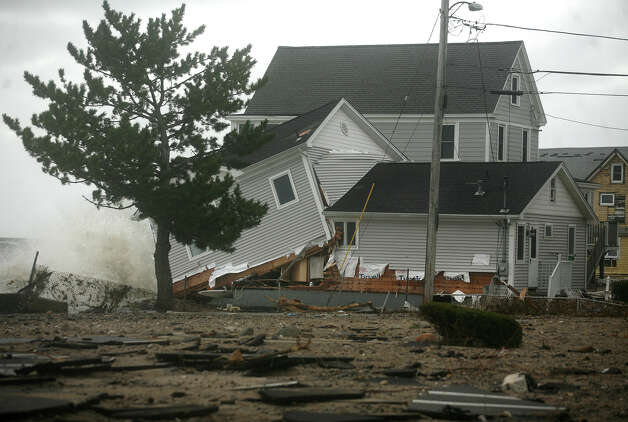 A badly damaged home continues to be hit by the waves in the aftermath of Hurricane Sandy on Ann Street in Milford on Tuesday, October 30, 2012. Photo: Brian A. Pounds