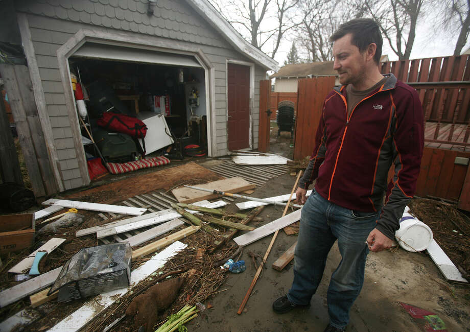 Derek Wilson looks at debris washed up on his driveway by flood waters from Hurricane Sandy, on Coolridge Road in the Point Beach section of Milford on Tuesday, October 30, 2012. Photo: Brian A. Pounds
