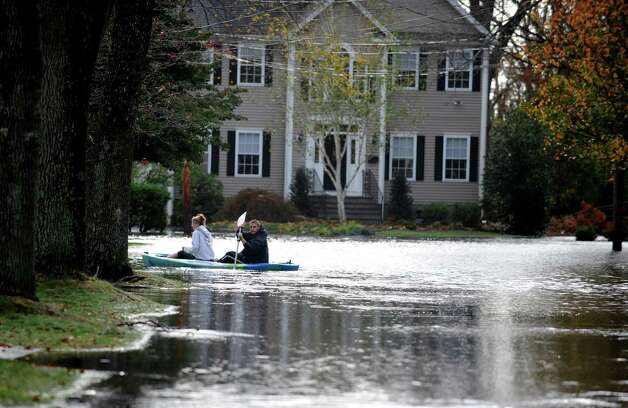 Kayakers turn onto Mellow Street from Old Field Drive in Fairfield, Conn. Tuesday, Oct. 30, 2012.  Hurricane Sandy flooded several roads in the town. Photo: Autumn Driscoll