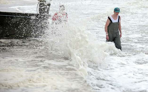 Men walk through the surf on their way to inspect damage to their home Tuesday, Oct. 30, 2012 on Fairfield Beach Road in Fairfield, Conn. Photo: Autumn Driscoll