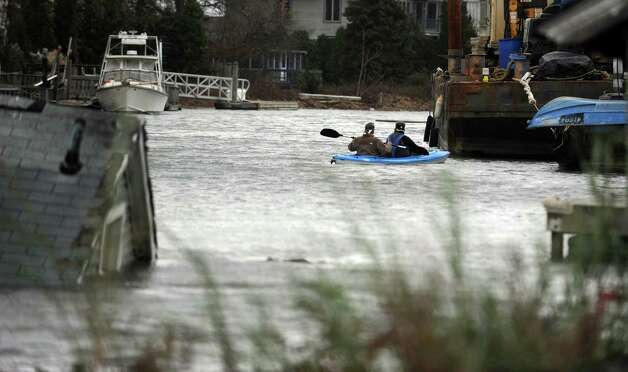 People kayak in Pine Creek near a house that came off its foundation during Hurricane Sandy and floats in the creek Tuesday, Oct. 30, 2012 in Fairfield, Conn. Photo: Autumn Driscoll