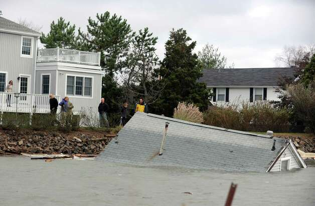 Residents watch from their yards on Old Dam Road as a house floats down Pine Creek Tuesday, Oct. 30, 2012 in Fairfield, Conn. Photo: Autumn Driscoll