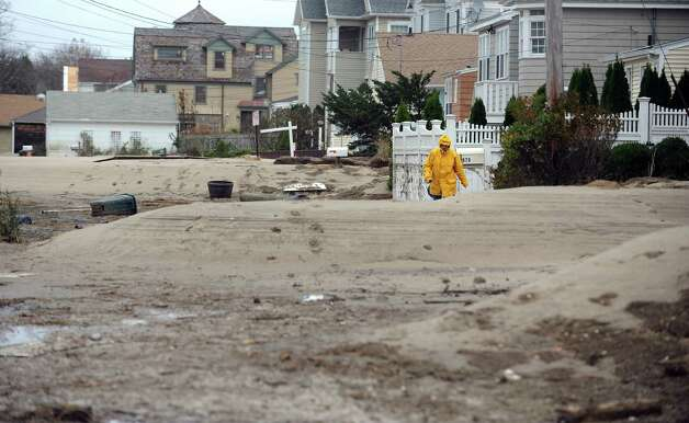 Donna Russo walks down Fairfield Beach Road Tuesday, Oct. 30, 2012 in Fairfield, Conn.  Sand dunes blown in during Hurricane Sandy completely cover the street. Photo: Autumn Driscoll