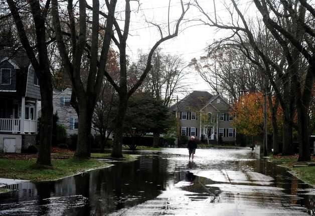 A man wades down Old Field Drive in Fairfield, Conn. Tuesday, Oct. 30, 2012.  Hurricane Sandy flooded several roads in the town. Photo: Autumn Driscoll