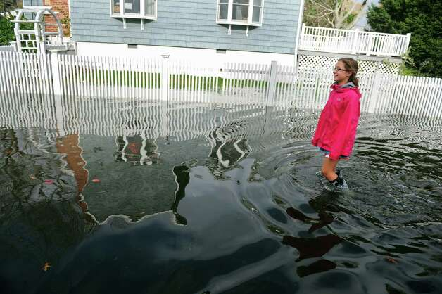 Lauren Beccaria, 12, walks through flood waters on Mellow Street in Fairfield, Conn. Tuesday, Oct. 30, 2012.  Residents estimated flood waters from Hurricane Sandy reached over 5 feet in their homes. Photo: Autumn Driscoll
