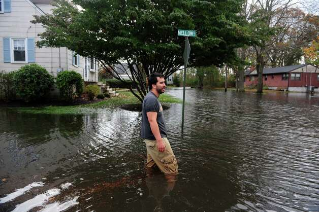 Sloane Yavarkovsky stands in knee deep water in front of his home on Mellow Street in Fairfield, Conn. Tuesday, Oct. 30, 2012.  Yavarkovsky said flood waters from Hurricane Sandy covered the second step to his home, behind him. Photo: Autumn Driscoll