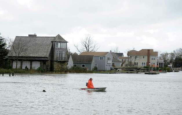 A man surveys damage from his boat on Pine Creek Tuesday, Oct. 30, 2012 in Fairfield, Conn. Photo: Autumn Driscoll