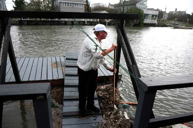 Jack Wrabel clears debris from his dock on Pine Creek Tuesday, Oct. 30, 2012 off Old Dam Road in Fairfield, Conn. Photo: Autumn Driscoll