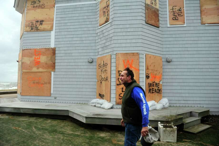 Paul Zecchi walks past his house, which was spared damage during Hurricane Sandy, Tuesday, Oct. 30, 2012 on Fairfield Beach Road in Fairfield, Conn. Photo: Autumn Driscoll