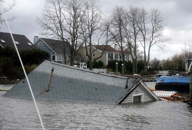 A house that came off its foundation during Hurricane Sandy floats down Pine Creek Tuesday, Oct. 30, 2012 in Fairfield, Conn. Photo: Autumn Driscoll