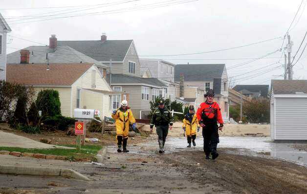 Members of the Fairfield Fire Department survey damage on Fairfield Beach Road Tuesday, Oct. 30, 2012 in Fairfield, Conn. Photo: Autumn Driscoll