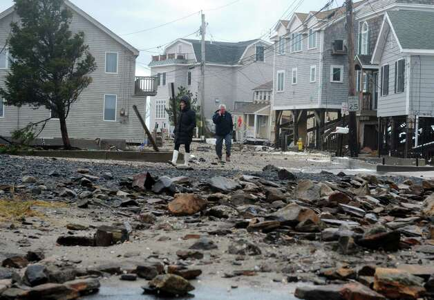 Susan Lane and Gus Costalvo wake down Fairfield Beach Road surveying damage Tuesday, Oct. 30, 2012 in Fairfield, Conn. Photo: Autumn Driscoll