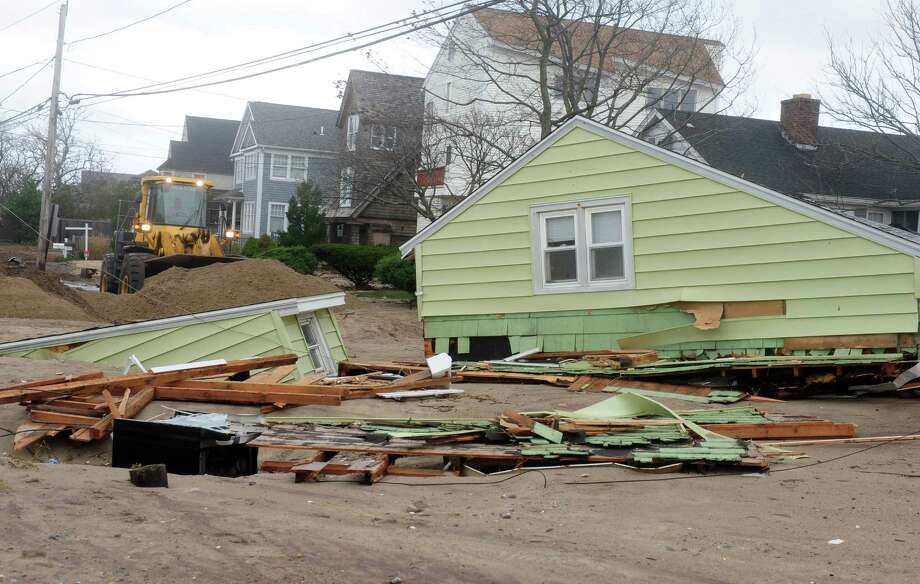 A crew works to clear sand deposited during Hurricane Sandy from Fairfield Beach Road Tuesday, Oct. 30, 2012 in Fairfield, Conn. Photo: Autumn Driscoll
