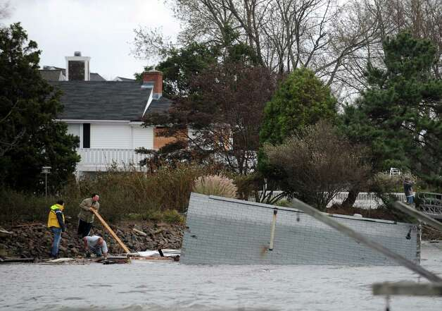 Residents off Pine Creek try to steer a house that came off its foundation during Hurricane Sandy away from shore Tuesday, Oct. 30, 2012 in Fairfield, Conn. Photo: Autumn Driscoll
