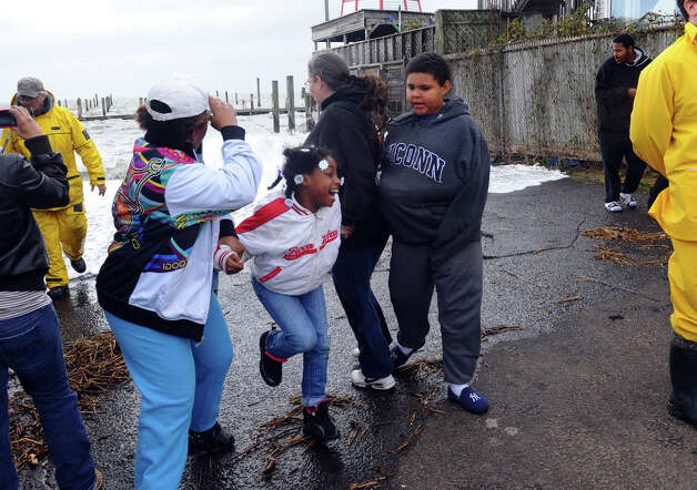 Keyani Smith, 6, of Bridgeport, starts to run away as water from the Long Island Sound splashes her and her family at the end of Newfield Avenue in Bridgeport, Conn. on Tuesday October 30, 2012. Photo: Christian Abraham