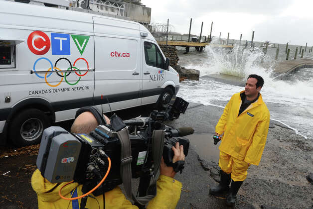 Paul Bliss, a reporter with CTV out of Toronto, Cananda, waits to do a report in front of the Long Island Sound at the end of Newfield Avenue in Bridgeport, Conn. on Tuesday October 30, 2012. Photo: Christian Abraham