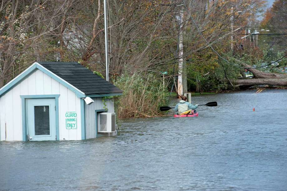 A kayaker paddles down the entrance road to South Benson Marina in Fairfield, Conn. on Tuesday, Oct. 30, 2012. Storm surge from Hurricane Sandy flooded the area. Photo: Mark Conrad