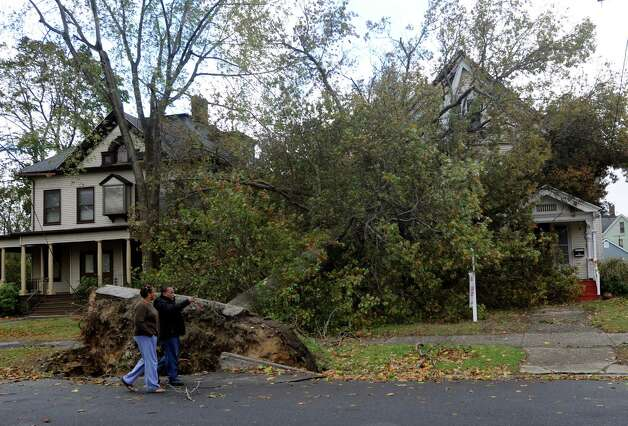 A huge tree fell on the Al Manar Center at 525 Clinton Ave. in Bridgeport, Conn. during the winds caused by Hurricane Sandy. People were out looking at the damage on Tuesday, Oct. 30, 2012. Photo: Cathy Zuraw
