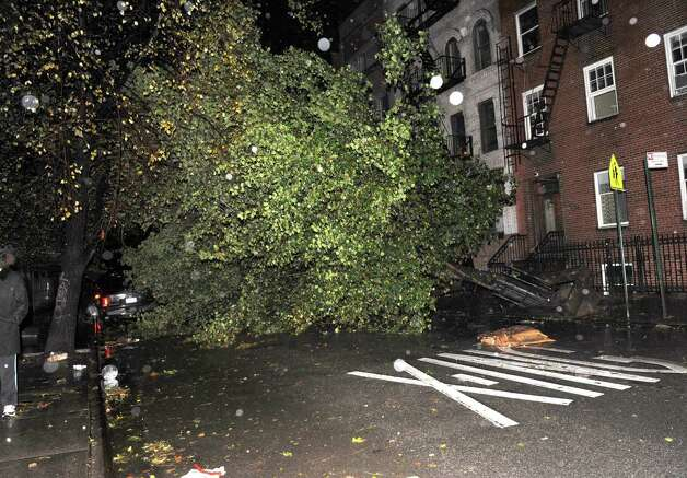 An uprooted tree blocks 7th street near Avenue D in the East Village as a result of high winds from Hurricane Sandy, Monday, Oct. 29, 2012, in New York. (AP Photo/Louis Lanzano) Photo: Louis Lanzano