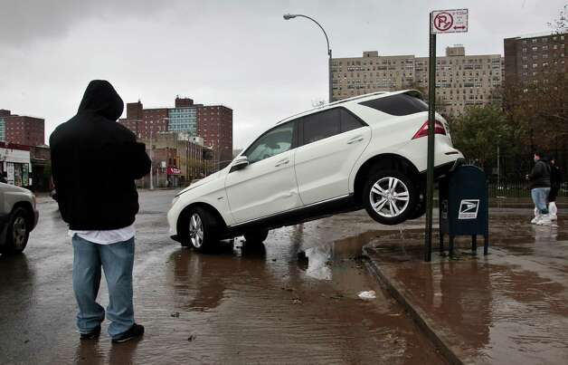 The tailend of a SUV is perched on top of a postal mailbox in the aftermath of floods from Hurricane Sandy on Tuesday, Oct. 30, 2012, in Coney Island, N.Y. Sandy, the storm that made landfall Monday, caused multiple fatalities, halted mass transit and cut power to more than 6 million homes and businesses. (AP Photo/Bebeto Matthews) Photo: Bebeto Matthews