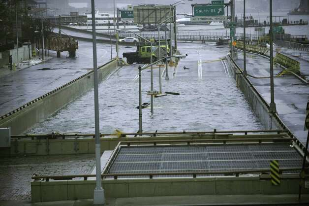 Water reaches the street level of the flooded Battery Park Underpass, Tuesday, Oct. 30, 2012, in New York. New York City awakened Tuesday to a flooded subway system, shuttered financial markets and hundreds of thousands of people without power a day after a wall of seawater and high winds slammed into the city, destroying buildings and flooding tunnels. (AP Photo/ Louis Lanzano) Photo: Louis Lanzano