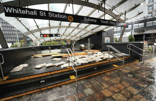 Sandbags block the entrance to the closed South Ferry/Whitehall Street subway station in Battery Park, Tuesday, Oct. 30, 2012, in New York. Sandy arrived along the East Coast and morphed into a huge and problematic system, putting more than 7.5 million homes and businesses in the dark and causing a number of deaths. (AP Photo/Louis Lanzano) Photo: Louis Lanzano